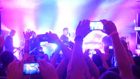 Fans hands recording video and taking pictures with smart phones at music concert. People crowd partying at rock concert Royalty Free Stock Photography