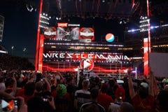 Fans jubeln zu und notieren Aktion an den Telefonen am Abschluss von Wrestlemania Stockfoto