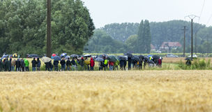 Fans of Le Tour de France. Ennevelin, France - July 09,2014: Cycling fans waiting for the peloton on a very bad weather in the field in North of France on the Stock Images