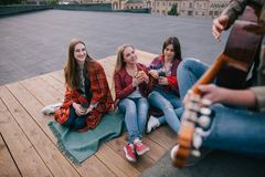 Fans on live music show. Friends leisure. Girls with fast food in hands listen singer`s acoustic guitar improvisation Stock Images