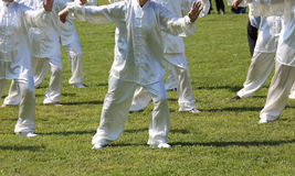 Fans of martial arts Tai Chi with white silk dress during the co Stock Photo