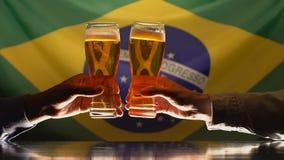 Fans masculinas que tintinean los vidrios de cerveza, equipo de apoyo, bandera brasileña en fondo almacen de video