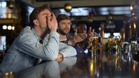 Fans masculinos infelices que miran el juego del deporte en el pub, decepcionado con el partido perdidoso metrajes
