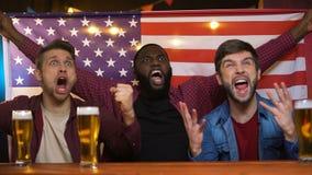 Fans masculinos multiétnicos americanos que celebran la victoria preferida del equipo, bandera que agita almacen de metraje de vídeo