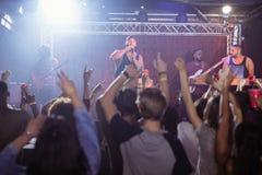 Fans med armar lyftte att tycka om på musikfestivalen Fotografering för Bildbyråer