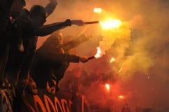 Fans mettant le feu à des feux d'artifice Photo stock