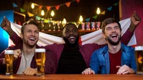 Fans multiraciales gaies soutenant l'équipe de football, tenant le drapeau anglais, passe-temps image stock