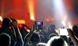 Fans nehmen Bilder und Aufzeichnungsvideos mit modernem Smartphones dur Stockfoto