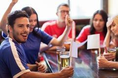 Fans ou amis observant le football à la barre de sport Photographie stock