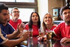 Fans ou amis observant le football à la barre de sport Images libres de droits