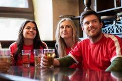 Fans ou amis observant le football à la barre de sport Image stock