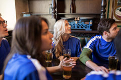 Fans ou amis observant le football à la barre de sport Image libre de droits