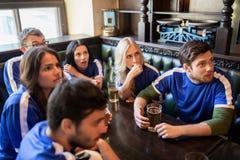 Fans ou amis observant le football à la barre de sport Photographie stock libre de droits
