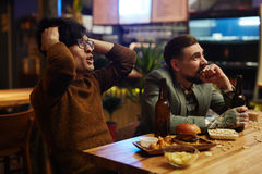 Fans in pub. Tense football fans watching match broadcast in pub Stock Image