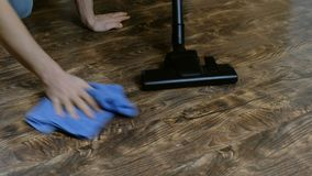 Fans of purity. A man and a woman is cleaning the floor and vacuuming the laminate. 4K.  stock footage