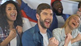 Fans que agitan la bandera inglesa que celebra la meta del equipo de deportes nacional, campeonato almacen de metraje de vídeo