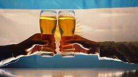 Fans que tintinean los vidrios de cerveza, bandera argentina en el fondo, ayuda del equipo de deportes metrajes