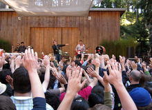 Fans raise hands at concert by They Might Be Giant. 73rd Stern Grove Festival: Fans raise hands in the air during a song by They Might Be Giants as singer on the royalty free stock photos
