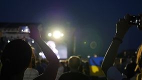 Fans records concert on cellphones, on background flag Ukraine, audience at rock concert with android, public with stock footage