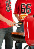 Fans: Sausages on the Grill. Extensive series, of male and female fans of American football. Watching from a couch, tailgating, and more royalty free stock images