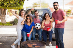 Fans of a soccer team grilling burgers at the game. Five excited soccer fans and friends watching a game while grilling some burgers and drinking beer stock image