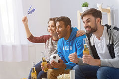 Fans of soccer watching match. Big screen sports viewing at home. Group of excited and happy football fans watching soccer match at home with beer Royalty Free Stock Photo