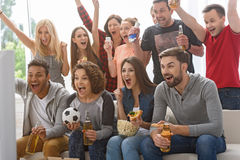 Fans of soccer watching match. Finally we have got first goal. Group of happy friends rooting for their soccer team on TV and celebrating goal Royalty Free Stock Photography