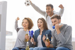 Fans of soccer watching match. Football is their great common passion. Screaming group of young football fans watching television with beer and soccer attributes Stock Images