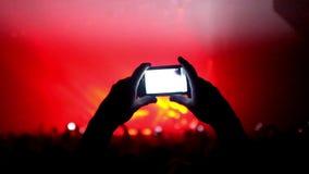 Fans som vinkar deras händer och, rymmer telefonen med digitala skärmar lager videofilmer