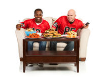 Fans: Two Dudes Watching TV With Snacks. Extensive series, of male and female fans of American football. Watching from a couch, tailgating, and more stock images