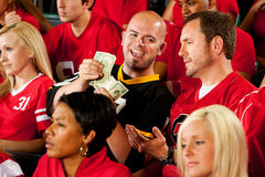 Fans: Visiting Team Fan Counts Money from Bet Stock Image