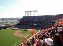 Fans wave orange towels to celebrate giants hit Royalty Free Stock Images