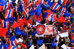 Fans waving flags at football game Royalty Free Stock Photos