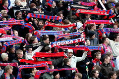 Fans waving scarfs at football game stock image
