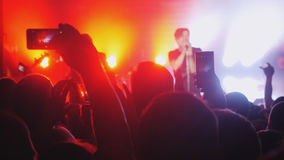 Fans waving their hands and hold the phone with digital displays the crowd at a rock concert. Blurred people crowd partying at rock concert in night club Stock Photos