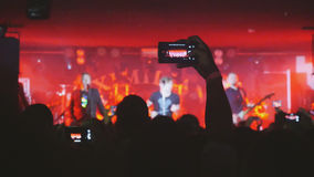 Fans waving their hands and hold the phone with digital displays the crowd at a rock concert. People crowd partying at a concert or a night club Royalty Free Stock Photography