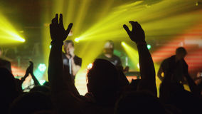 Fans waving their hands. People crowd partying at rock concert in night club. Stock Image