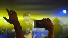 Fans waving their hands recording video and taking pictures with smart phones at rock concert. Royalty Free Stock Image