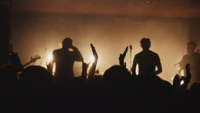 Fans waving their hands at a rock concert. Crowd partying at a concert. Stock Images