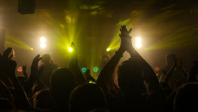 Fans waving their hands at rock concert in night club on beautiful golden lights Royalty Free Stock Images
