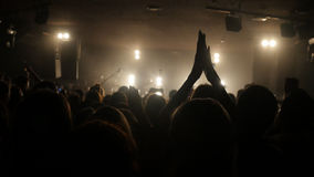Fans waving their hands at rock concert in night club on beautiful golden lights. Fans waving their hands and hold the phone with digital displays the crowd at a Royalty Free Stock Photography