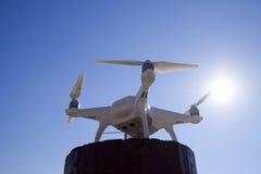 Fantôme 4 de Quadrocopter contre le ciel bleu au soleil Backligh Photographie stock