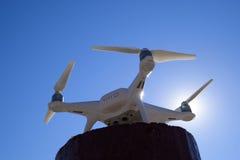 Fantôme 4 de Quadrocopter contre le ciel bleu au soleil Backligh Photographie stock libre de droits