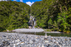 Stack of rocks and Fantail Falls at Mt Aspiring National Park, New Zealand. Fantail Falls is located in Mt Aspiring National Park, along HAAST Highway stock image