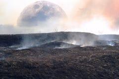 Fantasi av yttersidan av en annan planet med bränd till kol och bränd till kol jord och rök med en sikt av månen Arkivfoton