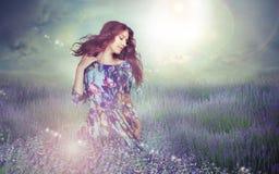 fantasi Kvinna i gåtfull äng över molnig himmel arkivfoto