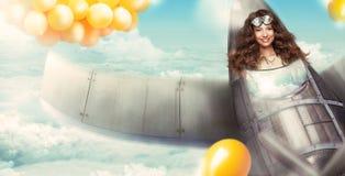 fantasi Lycklig kvinna i cockpit av flygplan som har gyckel royaltyfri bild
