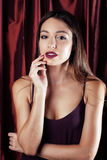A fantasia consideravelmente à moda da mulher dos jovens vestiu-se na cortina vermelha pronta para a celebração do partido, conce imagem de stock royalty free