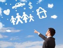 Fantasia do homem de negócios com as nuvens da família e do agregado familiar Fotografia de Stock Royalty Free
