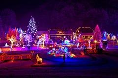 Fantasia do Natal - árvores e casas nas luzes Fotografia de Stock